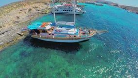 Os iate com turistas estão perto de uma costa de mar pitoresca Silhueta do homem de negócio Cowering malta Seascape maravilhoso c filme