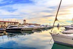 Os iate, o motor e os barcos de navigação luxuosos entraram no porto no por do sol Fotos de Stock