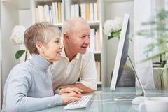 Os idosos olham o PC com curiosidade fotografia de stock