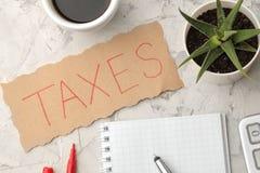 Os impostos da palavra em uma folha de papel em um caderno com café e na pena em um fundo do betão leve Vista de acima imagens de stock royalty free