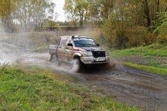 Os impulsos do carro da reunião 4wd molham o obstáculo cercado perto espirram Imagem de Stock