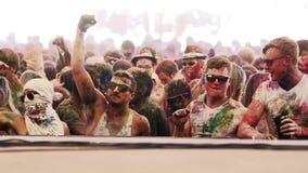 Os indivíduos brancos cobertos no pó dançam no festival da cor do holi no movimento lento filme