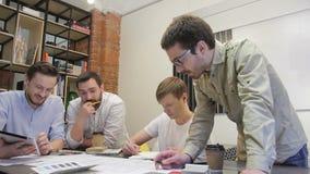 Os indivíduos engraçados com uma barba fazem um desenho no desktop video estoque