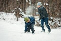Os indivíduos estão jogando na neve no inverno Imagens de Stock