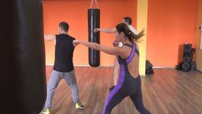 Os indivíduos são um homem e uma menina envolvidos no encaixotamento, treinando com um instrutor individual, artes marciais, somb video estoque