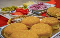 Os ingredientes caseiros do hamburguer arranjaram na bandeja e nas placas fora Cebola, pepinos salgados, tomates de cereja, molho imagem de stock