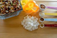 Os ingredientes crus incluem cebolas, pimentas de sino, feijões da sopa, e especiarias fotos de stock