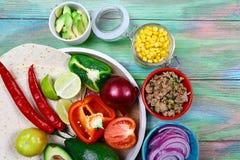 Os ingredientes para Burritos envolvem a carne, o milho, os tomates e as pimentas no fundo de madeira Vista superior fotos de stock