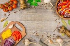 Os ingredientes para a cebola do alimento salpicam o alho e os utensílios em uma tabela de madeira ideia superior de verdes dos v Foto de Stock