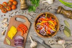 Os ingredientes para a cebola do alimento salpicam o alho e os utensílios em uma tabela de madeira ideia superior de verdes dos v Foto de Stock Royalty Free