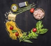 Os ingredientes para cozinhar a massa com camarão, ervas, tomates, queijo alinharam o lugar do quadro para a opinião superior do  foto de stock