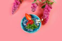 Os ingredientes para a desintoxicação da morango molham com a flor no fundo cor-de-rosa Bebida congelada verão Morango fresca Die imagem de stock