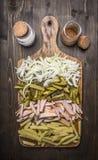 Os ingredientes para fazer o guisado de carne para Georgian, placa de corte, cebolas cortadas, presunto, conservam o backg rústic Imagem de Stock