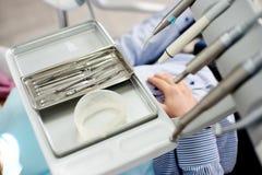 Os instrumentos dentais estão sendo indicados em uma bandeja médica de prata em um escritório dental fotografia de stock royalty free
