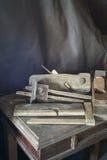 Os instrumentos do marceneiro idoso a descansar em cima da tabela de madeira Fotografia de Stock