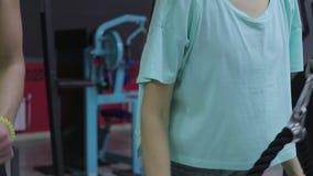 Os instrutores da aptidão mostram como fazer o exercício para o tríceps filme