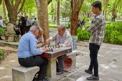 Os iranianos idosos jogam a xadrez no parque, Isfahan, Irã imagens de stock royalty free