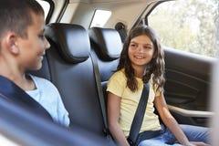Os irmãos de sorriso na parte de trás de um carro durante uma família tropeçam foto de stock royalty free