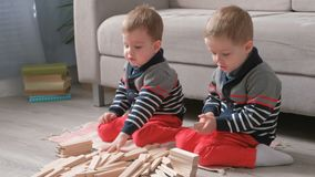 Os irmãos dos meninos dos gêmeos estão construindo dos blocos de madeira que sentam-se no assoalho pelo sofá em sua sala video estoque
