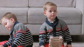 Os irmãos dos meninos dos gêmeos estão construindo dos blocos de madeira que sentam-se no assoalho pelo sofá em sua sala filme