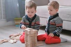 Os irmãos dos meninos dos gêmeos estão construindo dos blocos de madeira que sentam-se no assoalho pelo sofá em sua sala imagens de stock