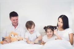 Os irmãos e a irmã leram um togather da história de horas de dormir Imagens de Stock Royalty Free