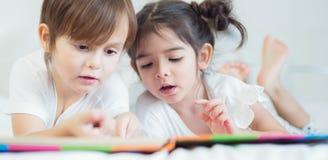 Os irmãos e a irmã leram um togather da história de horas de dormir na cama dentro Imagem de Stock