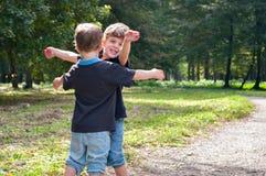 Os irmãos gêmeos idênticos alcançam para fora ao abraço Fotos de Stock
