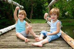 Os irmãos gêmeos pequenos adoráveis que sentam-se em uma ponte de madeira, guardando um peixe e apreciam sua captura no lago Imagem de Stock