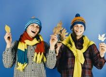 Os irmãos gêmeos que vestem irmãos secos mornos das folhas da posse dos chapéus e dos scarves apreciam o tempo do outono Tempo do Imagem de Stock Royalty Free