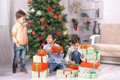Os irmãos ou os amigos dos meninos das crianças olham presentes sob um Natal Imagem de Stock