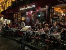 Os jantares da noite aglomeram-se fora das tabelas no restaurante de Montmartre imagens de stock royalty free