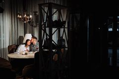 Os jantares de um par em um restaurante um homem beijam uma mulher fotografia de stock royalty free