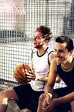 Os jogadores de basquetebol tomam uma ruptura que senta-se em uma baixa parede Imagens de Stock
