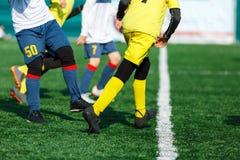 Os jogadores de futebol novos pingam e retrocedem a bola do futebol no jogo Meninos no sportswear branco amarelo que corre no cam imagem de stock royalty free
