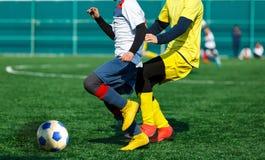 Os jogadores de futebol novos pingam e retrocedem a bola do futebol no jogo Meninos no sportswear branco amarelo que corre no cam imagens de stock royalty free