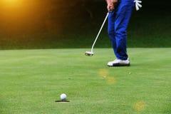 Os jogadores de golfe estão pondo o golfe no campo de golfe da noite em Tailândia foto de stock