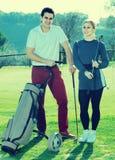 Os jogadores de golfe masculinos e fêmeas prontos para a equipe jogam no campo de golfe Imagens de Stock Royalty Free