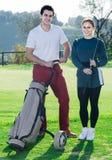 Os jogadores de golfe masculinos e fêmeas prontos para a equipe jogam no campo de golfe Foto de Stock Royalty Free