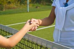 Os jogadores de tênis agitam as mãos antes e depois do fósforo do tênis Em Imagem de Stock Royalty Free