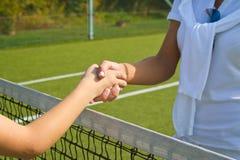Os jogadores de tênis agitam as mãos antes e depois do fósforo do tênis Na foto olha como a agitação das mãos que cumprimentam-se Fotografia de Stock Royalty Free