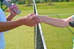 Os jogadores de tênis agitam as mãos antes e depois do fósforo do tênis Na foto olha como a agitação das mãos que cumprimentam-se Fotos de Stock Royalty Free