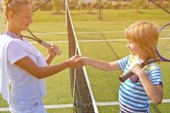 Os jogadores de tênis agitam as mãos antes e depois do fósforo do tênis Na foto olha como a agitação das mãos que cumprimentam-se Foto de Stock Royalty Free