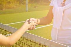 Os jogadores de tênis agitam as mãos antes e depois do fósforo do tênis Na foto olha como a agitação das mãos que cumprimentam-se Imagens de Stock Royalty Free