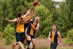 Os jogadores saltam para travar a bola no jogo de futebol das regras do australiano Imagem de Stock Royalty Free