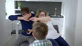 Os jogos de vídeo, criança precisam a atenção dos pais com o controlador do jogo nas mãos em casa video estoque