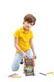 Os jogos do menino com lápis coloridos Imagens de Stock