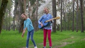 Os jogos exteriores das crianças, amigas alegres saltam comummente com guitarra à disposição no parque na primavera vídeos de arquivo