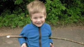 Os jogos felizes do rapaz pequeno com haste riem e sorriem filme