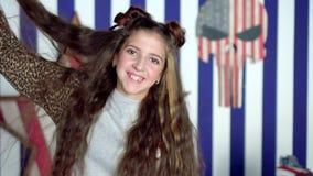 Os jogos morenos da menina com o cabelo A morena de cabelos compridos bonita no estúdio tem o divertimento na frente do vídeos de arquivo
